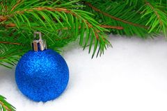 Blue New Year ball with green fir tree on snowy background stock photos