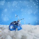 Blue New Year`s ball in the snow. Christmas card with blue ball on a blue background Royalty Free Stock Photos