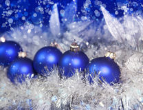 Blue New Year's balls and ribbon on a blue background Stock Photos
