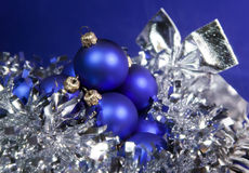 Blue New Year's balls and ribbon on a blue background Royalty Free Stock Photography