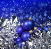 Blue New Year's balls and tinsel on a blue background Stock Photos