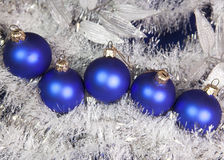Blue New Year's balls and tinsel on a blue background Stock Image