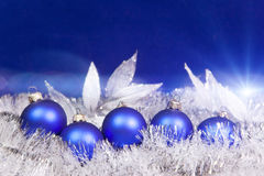 Blue New Year`s balls and tinsel on a blue background Royalty Free Stock Photography