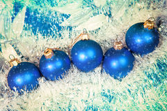 Blue New Year's balls and tinsel on a blue background. Used toning of the photo. Stock Photos