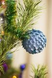 Blue New Year`s sphere on a fir-tree, a garland and tinsel. new year stock photo