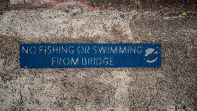 Blue No Fishing or Swimming From Bridge Sign on Weathered, Aged Concrete.  stock images