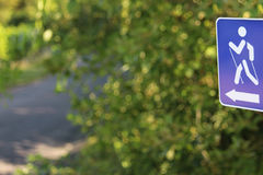 Blue nordic walking sign and a walking path Stock Photo