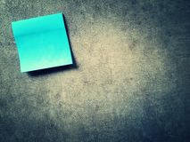 Blue note on grunge. Black blue post it note on grunge grey background Royalty Free Stock Images