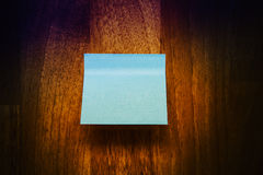 Blue note paper. On wooden texture Stock Photos