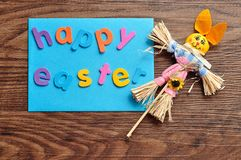 A blue note with the words happy easter and a bunny. On a wooden background Royalty Free Stock Image