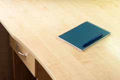 Blue notebook and blue pen on the desk Royalty Free Stock Image