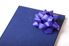 Blue notebook, calendar, book with a big blue round ribbon / bow decoration attached closeup, gift, knowledge. Concept royalty free stock image