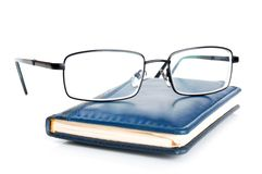 Blue notebook and glasses Stock Photos