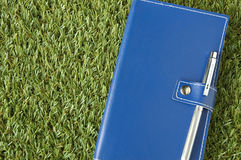 Blue notebook put on grass Royalty Free Stock Photography