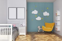 Blue nursery interior, posters and armchair. White and blue nursery interior with a gray bed, a yellow armchair, cloud decoration and two vertical posters. A Royalty Free Stock Photography