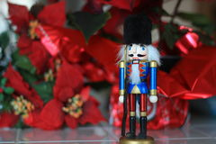 Blue nutcracker soldier toy. Nutcracker soldier toy with red pointsettias in the background Royalty Free Stock Image
