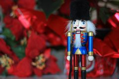 Blue nutcracker soldier toy. Nutcracker soldier toy with red pointsettias in the background Royalty Free Stock Images