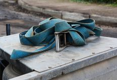 Blue strap with a metal buckle on a trailer. Blue nylon industrial strap with a metal buckle, piled on a metal trailer in a street undergoing repairs royalty free stock images