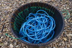 Blue Nylon Rope, black bin, pebbled beach. Blue nylon rope at the bottom of a black bin on a pebbled beach Royalty Free Stock Photos