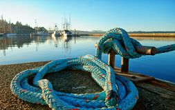 Blue nylon rope that ties the bow of a ship to a cleat fastened to a dock. royalty free stock photo