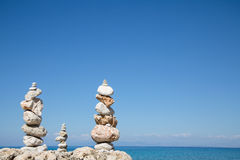 Blue ocean background with a pillar of stones for meditative or Royalty Free Stock Photo