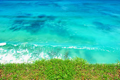 Blue ocean with blue sky horizon. Green grass with blue ocean and blue sky horizon background royalty free stock image