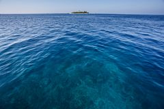 Blue sea with coral reef and small tropical island in the background Royalty Free Stock Photography
