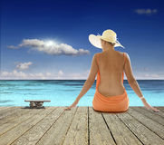 Blue ocean and the girl in the hat Stock Photos