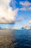 Blue ocean, light of large clouds reflected on surface, rainbow Royalty Free Stock Photos