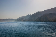 Blue ocean and mountains Stock Photography