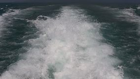 Blue ocean sea water wave with fast yacht boat wake foam of prop wash. Close up stock video