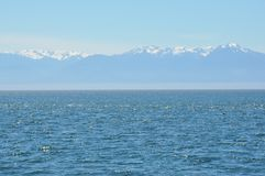 Blue Ocean and Snowy Mountains Royalty Free Stock Photo