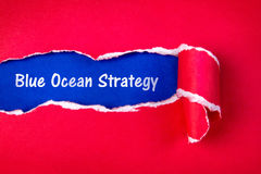Blue ocean strategy word on Torn red Paper and space with a blu. E paper background royalty free stock images