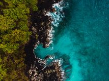Blue ocean in tropics with rocky coast. Aerial view stock photography