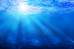 Blue ocean underwater sun rays background. Blue ocean underwater sun rays with bottom reflections background Stock Photo