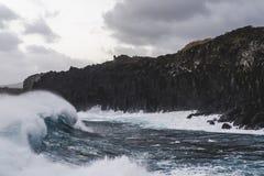 Blue Ocean Wave Crashes Againts Rocky Shore II stock images