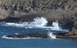 Blue ocean waves breaking on rocky coast Royalty Free Stock Photo