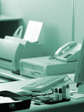 Blue office. Desk set up in a standard office environment, color-washed blue royalty free stock image