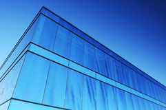 Blue office block. A modern office block with blue glass facade reflects a clear sky. Space for text in the sky Royalty Free Stock Photo
