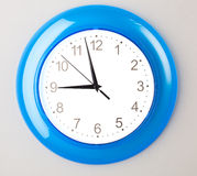 Blue office clock. On grey wall Royalty Free Stock Photography