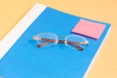 Blue office folder and glasses. On table royalty free stock photos