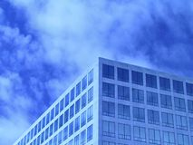 Blue Office Windows. Office windows in front of partially cloudy sky. Tinted blue. Plenty of room for text royalty free stock photos