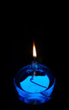 Blue Oil Candle. Lit blue oil candle against black stock photography
