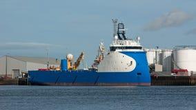 Blue Oil Platform Supply Ship. Oil platform supply vessel with inverted bow shape moored alongside oil storeage tanks Royalty Free Stock Photo
