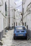 Iconic european street scene. Iconic european narrow paved street scene with tiny blue car Royalty Free Stock Photo