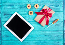 Blue old desk with tablet computer, gift box with bow, cookies with marmalade, lollipop. Top view. Flat lay Stock Photography