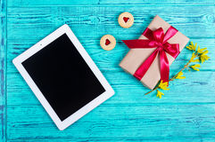 Blue old desk with tablet computer, gift box with bow, cookies with marmalade, spring flower. Top view. Flat lay Royalty Free Stock Images