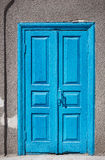 Blue old door. On background of gray wall Stock Photos