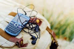 Blue old fashioned smart phone with  qwerty keypad on backpack. Blue old fashioned smart phone with  qwerty keypad and headset on backpack Royalty Free Stock Photo
