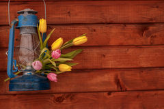 Blue old kerosene lamp with a bouquet of tulips on a wooden background. Blue old kerosene lamp with a bouquet of yellow tulips on a brown wooden background Stock Image